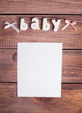 Word baby and white frame photo. On wood background Royalty Free Stock Images