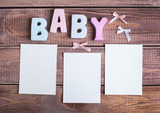 Word baby and white frame photo. On wood background Royalty Free Stock Photos