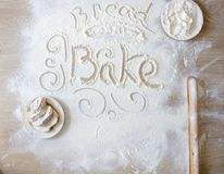 Word bake written in flour. Hand-drawn decorative elements. Plate with bread slices covered with white flour royalty free stock images