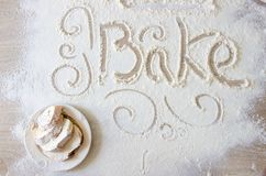Word bake written in flour. Hand-drawn decorative elements. Plate with bread slices covered with white flour stock photo