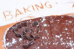 Word baking written in flour, cookie cutters and dough for gingerbread Royalty Free Stock Image