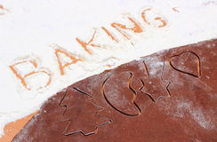 Word baking written in flour and shape of cookie cutters Royalty Free Stock Images