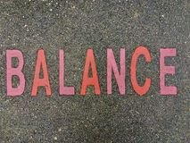 The word BALANCE on the floor in a kids park. The word BALANCE stencilled in pink and red letters onto the floor made out of wet pour rubber surface material in royalty free stock image