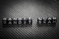 Word Bandit Scam of black cubes on a gray. royalty free stock photos