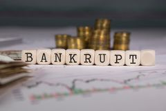 Word BANKRUPT composed of wooden letter. Stacks of coins in the background. Closeup stock image