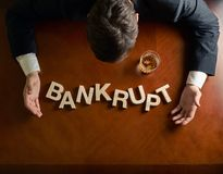 Word Bankrupt and devastated man composition. Word Bankrupt made of wooden block letters and devastated middle aged caucasian man in a black suit sitting at the stock photography