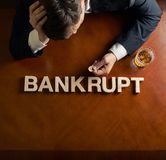 Word Bankrupt and devastated man composition. Word Bankrupt made of wooden block letters and devastated middle aged caucasian man in a black suit sitting at the stock image