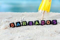 Word Barbados wordt gemaakt van multicolored brieven op sneeuwwit zand tegen het blauwe overzees Stock Fotografie