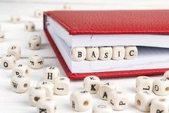 Word Basic written in wooden blocks in notebook on wooden table. Word Basic written in wooden blocks in red notebook on white wooden table stock photography