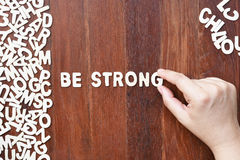 Word be strong made with block wooden letters. Next to a pile of other letters over the wooden board surface composition Stock Images