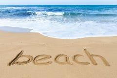 Word beach on sandy coast with blue sea Stock Photography