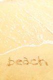 Word beach written in the sand of a beach Stock Images