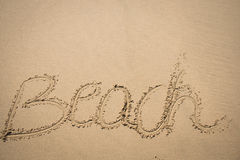 The word beach written in the sand Stock Image