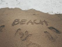 Word beach written in sand summer concept. Word beach and footprints in sand Royalty Free Stock Photography