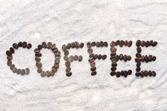 Word from beans coffee. On white sand Stock Image