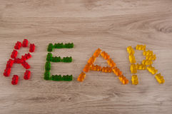 Word bear made of multicolored gummy bears on wooden background. Word bear made of red, green, orange, yellow gummy bears sweets lay on wooden background Stock Photography
