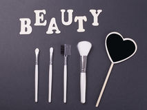 Word Beauty next to accessories for make-up on black background. Stock Image