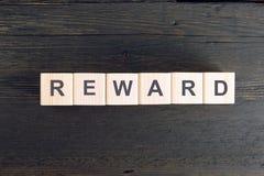 Word BELONING die op een houten kubus wordt geschreven Risico en beloningsconcept royalty-vrije stock foto's