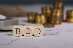 Word BID composed of wooden letter. Stacks of coins in the background. Closeup stock images