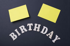 Word Birthday next to two yellow post-its on black background. Royalty Free Stock Photography