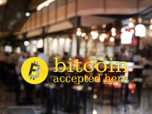Word bitcoin accepted here with blur restaurant background. royalty free stock photography
