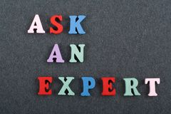 ASK AN EXPERT word on black board background composed from colorful abc alphabet block wooden letters, copy space for ad stock photos
