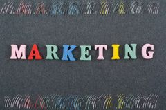MARKETING word on black board background composed from colorful abc alphabet block wooden letters, copy space for ad royalty free stock photography