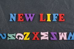NEW LIFE word on black board background composed from colorful abc alphabet block wooden letters, copy space for ad text. Word on black board background composed stock photos
