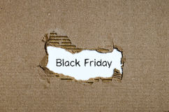 The word black friday appearing behind torn paper Stock Image