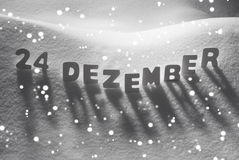 Word blanc 24 Dezember signifie le 24 décembre sur la neige, flocons de neige Photographie stock