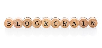 Word Blockchain from circular wooden tiles with letters children toy. stock illustration