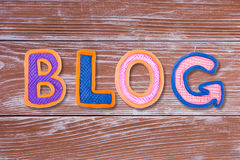 Word BLOG made with plasticine letters on old wooden board background. Stock Image