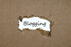 The word blogging appearing behind torn paper. The word blogging behind torn paper royalty free stock photos