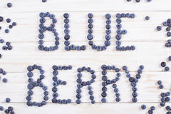 Word blueberry written letters with blueberries on white wooden Royalty Free Stock Photos
