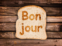 Word bonjour written on a toasted slice of bread Stock Photography