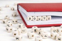 Word Bonus in houten blokken in notitieboekje dat op witte houten wordt geschreven stock foto