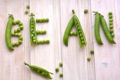 Word ` boon ` van ruwe, verse potten en erwtenachtergrond Spleet, groene erwten op houten raad Royalty-vrije Stock Foto's