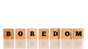 The word - Boredom- on wooden cubes. Arranged in a line on a reflective white surface with copyspace above Royalty Free Stock Photography