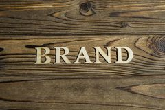 The word BRAND is lined with letters on a wooden background. stock photos