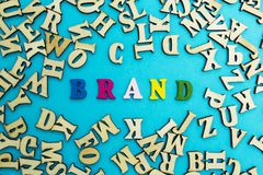 The word `brand` is lined with multicolored letters on a blue background royalty free stock image