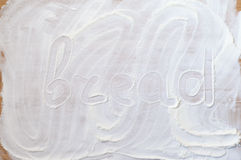 Word bread on wood board with flour Stock Image