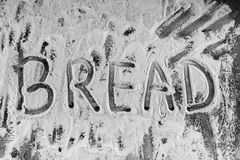 Word bread written in flour on table Stock Photography