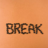 The word break spelled out in beans. Roasted coffee beans spelling out words on an orange background Royalty Free Stock Image