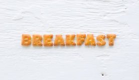Word BREAKFAST Alphabet crackers on wood background Royalty Free Stock Photography