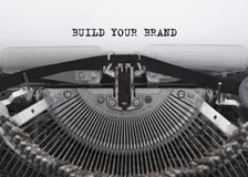 BUILD YOUR BRAND typed words on a vintage typewriter. The word BUILD YOUR BRAND printed on a sheet of paper on a typewriter. retro technique royalty free stock image