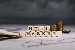 Word BULL MARKET composed of wooden letter. Stacks of coins in the background. Closeup royalty free stock photo
