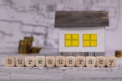 Word BUREAUCRACY composed of wooden letter. Small paper house in the background. Closeup royalty free stock photo