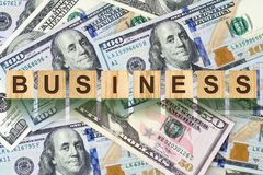 Word, Business composed of letters on wooden building blocks against the background of dollar bills. Concept business, finance. Backgrounds stock photo