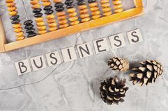 Word BUSINESS laid out of handwritten letters on cardboard squares near old wooden abacus and three cones. On gray cracked concrete royalty free stock photo