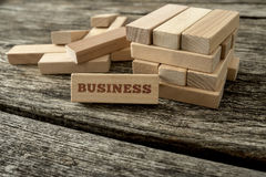 Word Business written on a wooden peg leaning on a structure bui Royalty Free Stock Photo